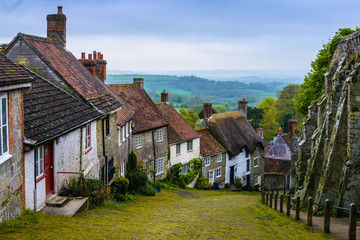A row of cottages on a steep cobbled street at Gold Hill in Shaftesbury, Dorset, United Kingdom, England. Great Britain
