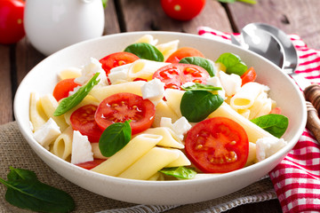 Pasta salad with fresh red cherry tomato and feta cheese. Italian cuisine