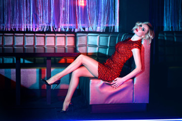 Beautiful blond model with provocative make up wearing red short fitted sequin dress and black high-heeled shoes relaxing on the square sofa in night club in colourful neon lights. Text space