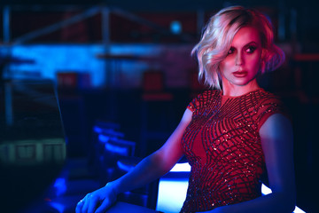 Close up portrait of beautiful glam blond woman with provocative make up wearing red sequin dress sitting at the bar in the night club in colourful neon lights and looking aside. Text space