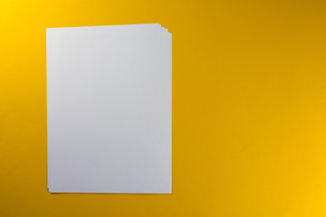 Blank sheets of paper yellow background