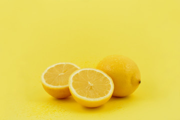 Yellow lemons stock images. Lemons on a yellow background. Juicy pieces of lemons