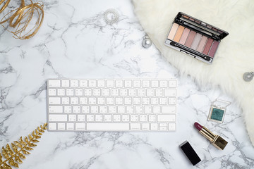 Top view of white keyboard  on luxury marble and fur  with cosmetic,lipstick and eyeshadow .
