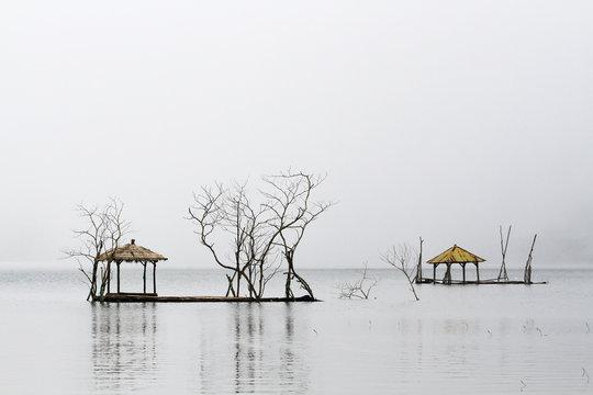 Fishing platforms on a misty Lake Tamblingan, Bali, Indonesia