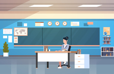School Classroom Interior Woman Teacher Sitting At Desk Over Chalk Board In Class Room Flat Vector Illustration