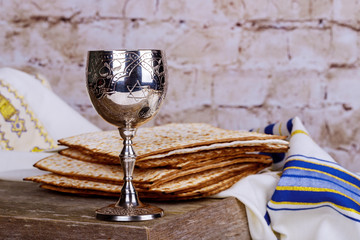Jewish holidays Passover Pesach matzah and a silver cup full of wine with a traditional blessing