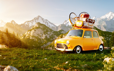Cute little retro car with suitcases and bicycle on top on grass field at mountain in summer day.