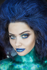 Portrait of a beautiful mermaid girl. Wet skin, wet hair, glitter and scales on his face. Blue eyes. The image on Halloween. Advertising Space