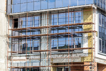 glass office building under construction. building site with scaffolding.