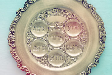 Pesah celebration concept (jewish Passover holiday). Traditional pesah plate text in hebrew: Passover, horseradish, celery, egg, bone, maror, charoset.