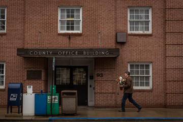 A man carries flowers outside a county office on Valentine's Day in Waynesburg
