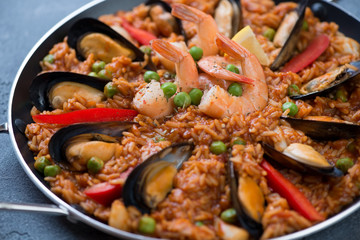 Close-up of spanish paella with mussels, tiger shrimps, calamari, green peas and red bell peppers slices, selective focus