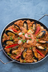 Frying pan with spanish traditional seafood paella over blue stone background, studio shot