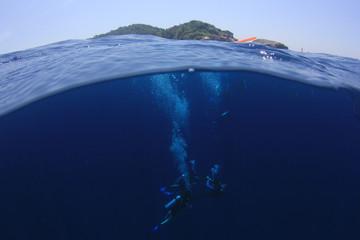 Scuba divers underwater half and half over under split photo