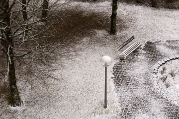 Park bench and slightly snow-covered ground from a bird's eye view