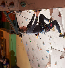 Female climber practicing indoors climbing rock wall at the sports center copyspace bouldering hobby lifestyle leisure active people extreme preparation.