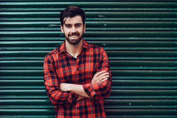 Young smiling man, model of fashion, wearing a plaid shirt with a green blind behind him.