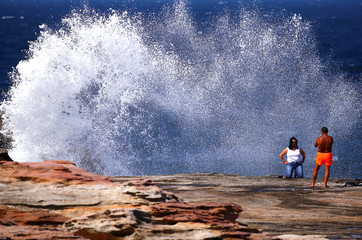 A man uses an iPhone to take a photograph of a woman as a large wave breaks on rocks behind her on a summer day at Maroubra Beach in Sydney