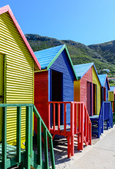 Famous colorful Victorian bathing boxes at St. James beach, Cape Town,South Africa, taken on a sunny clear bright day under blue sky with hills in the background