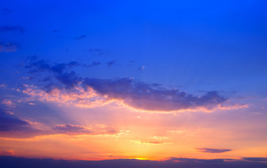 Beautiful colorful sunset sky background with the light of sun behind.Blue and purple clouds.