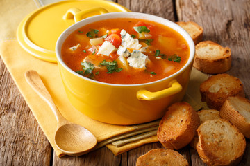 Hot buffalo soup with chicken, vegetables and blue cheese close-up in a saucepan and bread. horizontal, rustic style