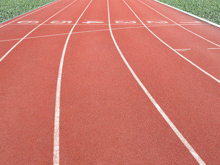 red running track with lane numbers and green grass in outdoor athletics stadium, empty starting point (or finish line) of running track, background for business competition or motivation concept