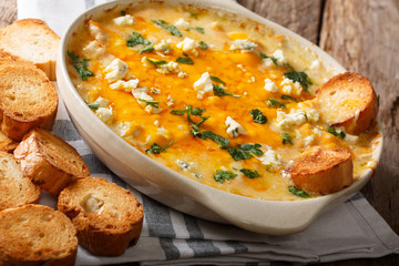 chicken buffalo dip with blue cheese and greens close-up in a baking dish on a table. horizontal