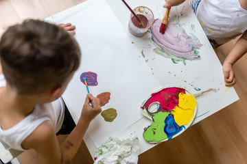 Two kids painting with water colors with brush