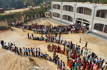 People stand in queues as they wait to cast their vote outside a polling station during Tripura state assembly election on the outskirts of Agartala