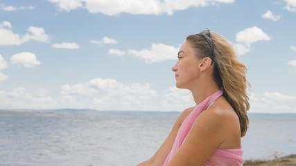 Beautiful woman is sitting on the beach. Joyful woman looks at the sea.