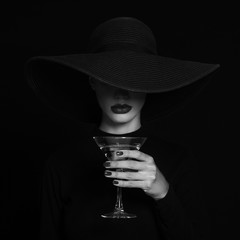 Luxury woman in a black hat with Martini glass in hand.