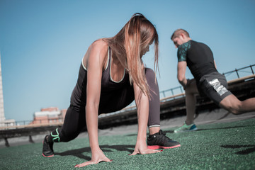 Sportive man and woman doing lunges outdoors. Young people training on the roof of the building.
