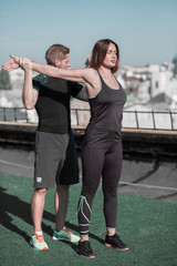 Man and woman working out together. Sport on the roof, couple doing sport exercises.