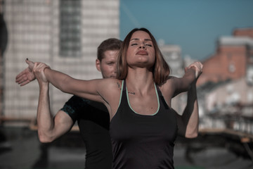Man and woman working out outdoors. Fitness on the roof concept, man helping young female to stretch arms and shoulders.