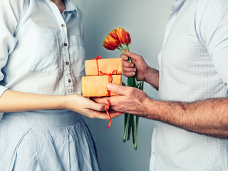 Handsome man giving a gift and flowers to his beloved woman