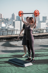 Young woman liting a barbell on the roof of the building. Sport exercises on the top of a building in the city.
