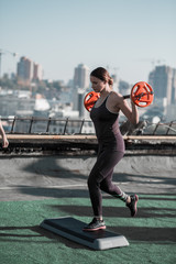 Attractive woman working out, doing lunges with weight. Healthy lifestyle, female and man training outdoors.