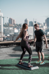 Sportive man and woman working out using step platform. Young couple practicing sport exercises together.