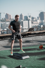 Man working out on the roof, using step platform. Sportive man doing cardio training, jumping.