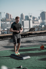 Young athletic man getting ready for workout on the roof. Sport exercises on the roof with nice city view.