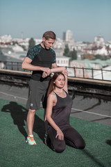 Sport on the roof with city view, man and woman working out. Personal trainer helping young female with stetching.