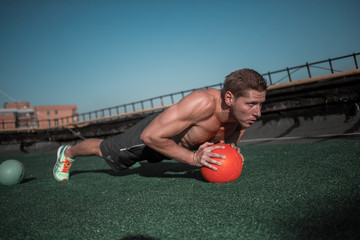 Young muscular man working out on the roof. Athletic male using ball to work out on abdominal muscules.