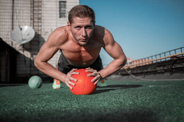 Front view of man standing in plank with hands on the ball. Sport exercises on the roof of the building.