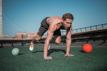 Strong young man doing sport exercises on the top of the buildig. Sport outdoors, muscular male training.