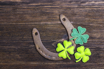 Rusty horseshoe and felt  clover leaves on wooden boards. St.Patrick's day holiday symbol. Lucky charms.