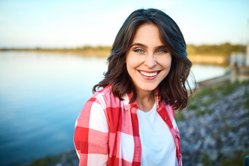 Portrait of beautiful young lady staring straight at camera smiling with view of lake in the background