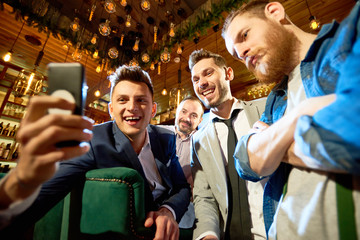 Smiling bearded friends taking selfie with help of smartphone while having long-awaited gathering in modern pub