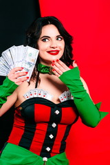 portrait of the beautiful smiling surprised of gain brunette woman with make up in red and black dress with cards with fake (souvenir) money (dollars) in her hands