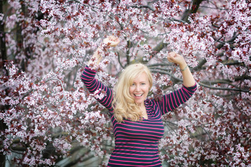 Blond long hair Caucasian woman happy and laughing near blossoming tree