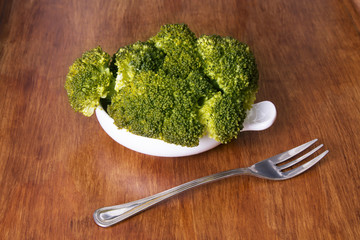 cooked broccoli with cutlery on top of wooden table